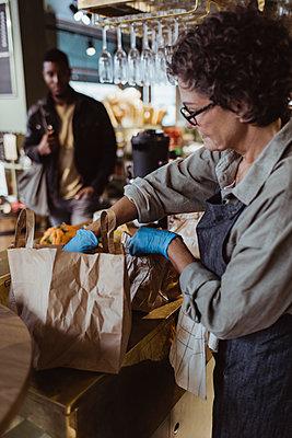 Female entrepreneur packing order in paper bag at delicatessen shop - p426m2270485 by Maskot