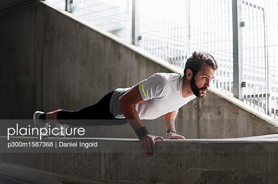 Man doing push-ups on concrete wall - p300m1587368 von Daniel Ingold