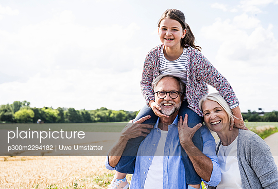 Cheerful man carrying granddaughter on shoulder while woman with during sunny day - p300m2294182 by Uwe Umstätter