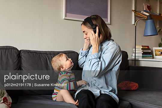 Mother with baby on sofa - p312m2191178 by Susanne Kronholm
