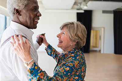 Happy active senior couple dancing in dance studio - p1023m2017251 by Martin Barraud