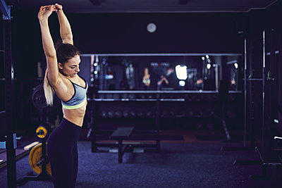 Side profile of young woman stretching at the fitness centre - p1166m2095537 by Cavan Images
