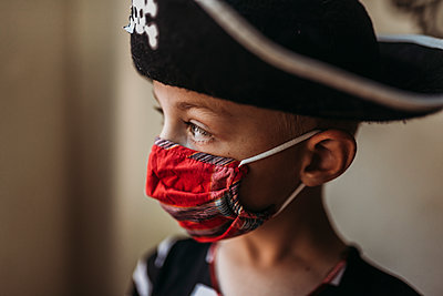 Lifestyle portrait of young boy dressed as pirate with face covering - p1166m2207775 by Cavan Images
