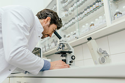Man using microscope in laboratory - p300m1549523 by Mareen Fischinger