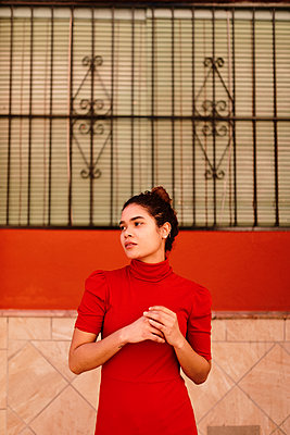 Portrait of melancholic woman with red dress looking sideways - p300m2171313 by Tania Cervián