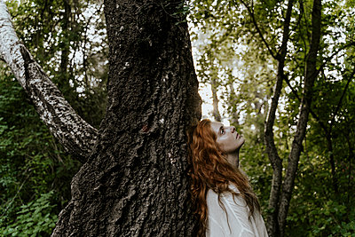 Young redhaired woman hugging tree trunk in forest - p300m2179924 by VITTA GALLERY