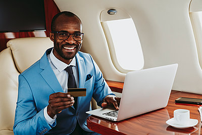 Smiling businessman with credit and laptop in private jet - p300m2257032 by OneInchPunch