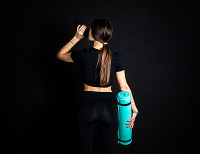Brown hair female athlete drinking water while holding exercise mat  - p300m2281944 by Giorgio Fochesato