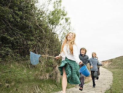 Children running along decking - p4296390f by Ashley Jouhar