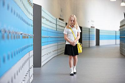 Unhappy schoolgirl walking alone in school corridor - p429m884618f by Phil Boorman