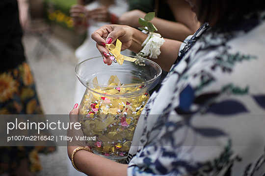 Woman pulls a wish out of glass container - p1007m2216542 by Tilby Vattard