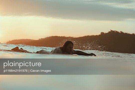 Surfer in sea at sunset,Lombok, Indonesia - p1166m2191976 by Cavan Images