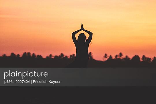 Brazil, Taiba, Sunset, Woman doing yoga  - p986m2227404 by Friedrich Kayser