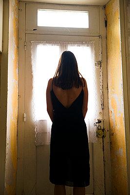 Woman standing next to an old door - p1096m1559161 by Rajkumar Singh