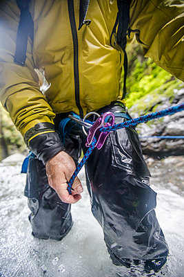 close up view of man using belay device while canyoning. - p1166m2138001 by Cavan Images