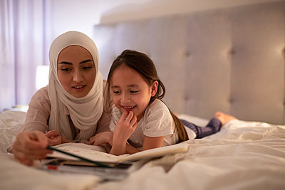 Muslim mother having virtual meeting at home - p1166m2234964 by Cavan Images