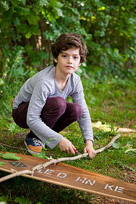 Junge schneidet Ast zurecht - p1195m1138102 von Kathrin Brunnhofer