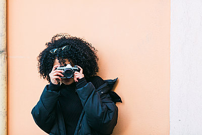 Young woman taking photograph against orange wall - p1427m2084967 by Alexandra C. Ribeiro