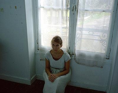 Frau sitzt an der Glastür - p945m716061 von aurelia frey