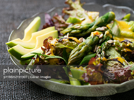 Vegan salad with asparagus on mixed greens with a tahini dressing. - p1166m2191907 by Cavan Images