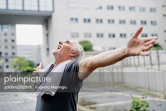 Cheerful senior man with arms outstretched standing against building in city - p300m2202916 by Eugenio Marongiu