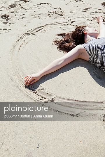 Young woman making patterns in sand - p956m1136860 by Anna Quinn