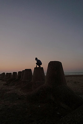 Person squatting on wave-breaker at sunset - p1151m1194866 by Laure Ledoux