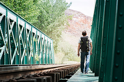 Rear view of man walking on railway bridge - p1166m1163873 by Cavan Images