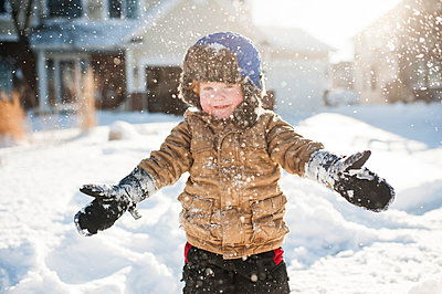 Toddler boy playing and smiling while throwing snow in front of house - p1166m2136756 by Cavan Images