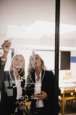 Mature and young businesswoman drawing chart on glass pane in office - p300m2170195 by Gustafsson