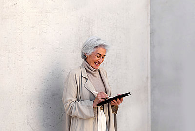 Happy woman using digital tablet in front of wall - p300m2281478 by PICUA ESTUDIO