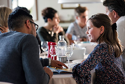 Smiling girl looking at man reading magazine while sitting with friends in dinner party - p426m1212748 by Maskot