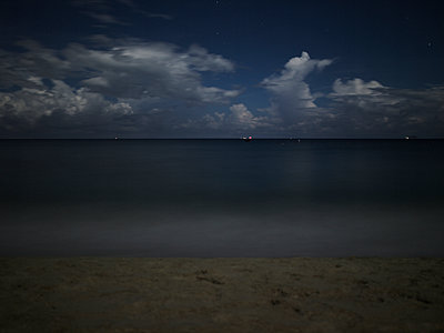 Mysteriously calm ocean waters at night in Dong Hoi, Vietnam, Southeast Asia - p934m892978 by Boris Zuliani