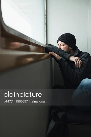 Depressiver junger Mann mit Strickmütze  - p1477m1586657 von rainandsalt