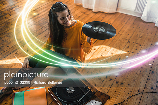 Young woman sitting on the floor at home with record and record player surrounded by a light trail - p300m2132398 by Richárd Bellevue