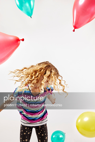 Blonde girl playing with balloons - p968m1128432 by roberto pastrovicchio