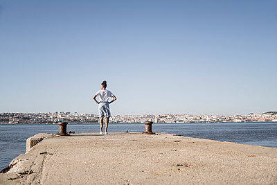 Young woman standing on pier at the waterfront, Lisbon, Portugal - p300m2144527 by Uwe Umstätter