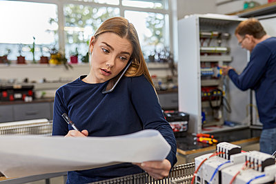 Young woman on the phone in electrical workshop - p300m2181224 by Zeljko Dangubic