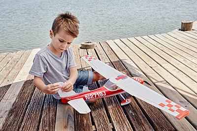 Südafrika, Westkap, Kapstadt, Bootssteg, Steg, Jetty, See, Junge mit Spielzeugflugzeug - p300m2267228 von Roger Richter