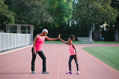 Grandmother and granddaughter high-fiving on track - p555m1304766 by Shestock