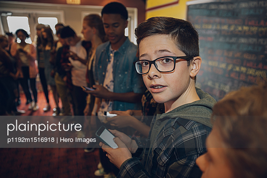 Portrait tween boy texting with smart phone, waiting in queue at movie theater - p1192m1516918 by Hero Images