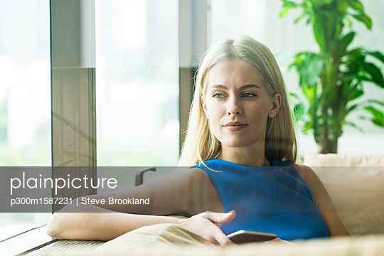 Portrait of attractive woman relaxing on couch at home - p300m1587231 von Steve Brookland