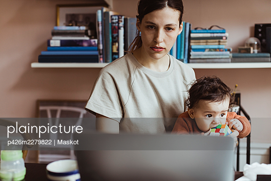 Businesswoman using laptop while sitting with baby boy at home - p426m2279822 by Maskot