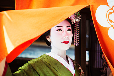 A woman dressed in the traditional geisha style, wearing a kimono with an elaborate hairstyle and floral hair clips, with white face makeup with bright red lips and dark eyes lifting an orange curtain.  - p1100m1185736 by Mint Images