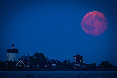 Moon over island lighthouse - p1418m1572001 by Jan Håkan Dahlström