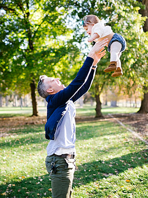 Father throwing daughter   up in air in park - p1427m1517425 by Jessica Peterson