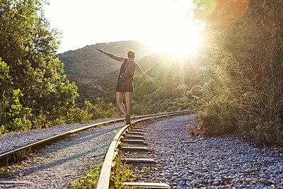 Greece, Pilion, Milies, back view of woman balancing along rails of Narrow Gauge Railway at sunset - p300m1580843 von Maria Maar