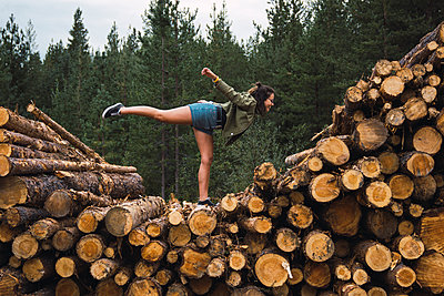 Young woman standing on one leg on stack of wood - p300m2060887 by Kike Arnaiz