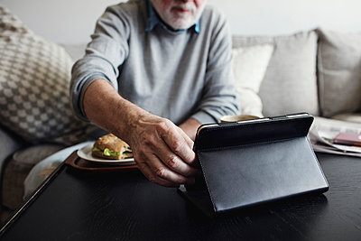 Senior man holding digital tablet while having breakfast at table - p426m1468340 by Maskot