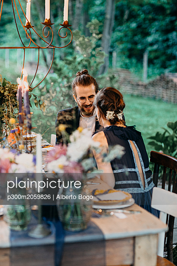Happy bride and groom sitting at festive laid table outdoors - p300m2059826 by Alberto Bogo